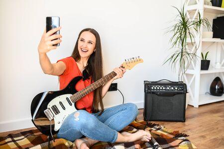 Junge positive Frau macht Selfie am Telefon mit einer E-Gitarre zu Hause, Combo-Verstärker in der Nähe. Sie sitzt auf einem gemütlichen Plaid auf dem Boden, schaut in die Smartphone-Kamera und lächelt. Standard-Bild