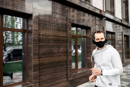 Healthy habits during quarantine. Young man in sports clothing in medical mask on the face is running while exercising outside