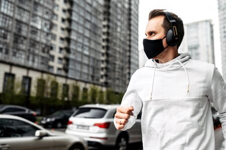 Keep yourself in shape during quarantine. Athletic young man is jogging in a protective mask among high-rise buildings. Healthy lifestyle concept Фото со стока
