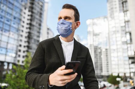 A young businessman in smart casual with a protective surgery mask on the face outdoors, he holds phone in hand and looks away
