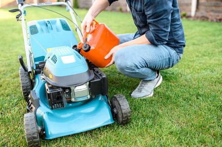 Gardening equipment in the backyard. Young guy in casual clothes refills a gas mower, the fase is not visible