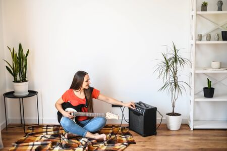 A young woman spends home leisure at quarantine with playing an electric guitar, she sits on a plaid on the floor and sets up a combo amp Foto de archivo