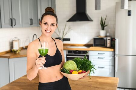 Body detox. Young attractive woman in sportswear in the kitchen with a glass of detox smoothie and a basket of vegetables in her hands Фото со стока