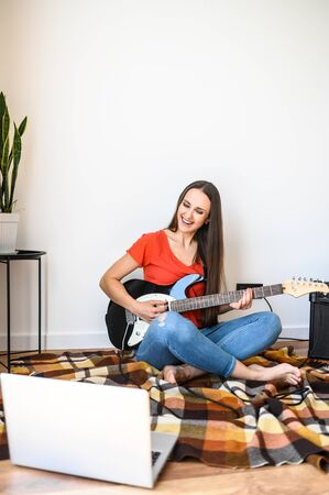 A young beauty girl is learning electric guitar playing with a video tutorial on laptop. She sits on cozy plaid with guitar in hands, combo amp near on the floor