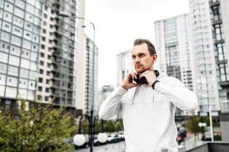 Sports lifestyle. Young athletic man in sportswear with headphones among city skyscrapers