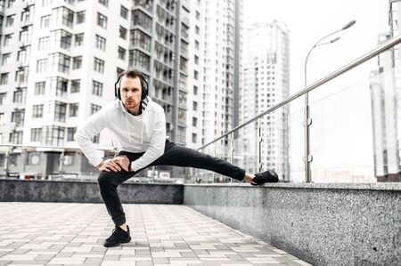 Stretching outdoors. A young man doing exercises among cityscape