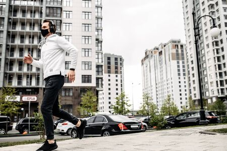 Healthy habits. Full length of young man in sports clothing in medical mask on the face is running while exercising outside Фото со стока