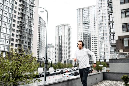 Get in shape. Young man in sportswear runs outdoors among the city skyscrapers Фото со стока