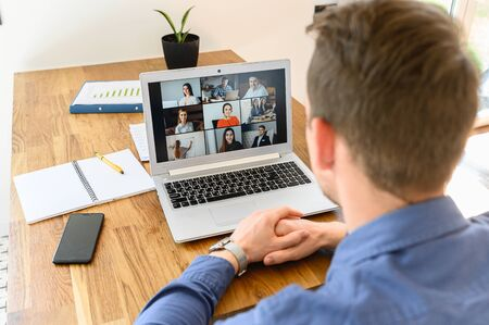 Webinars, online conference, video meeting. A businessman is using app on laptop for video connect with a many people at same time together. Distant work concept