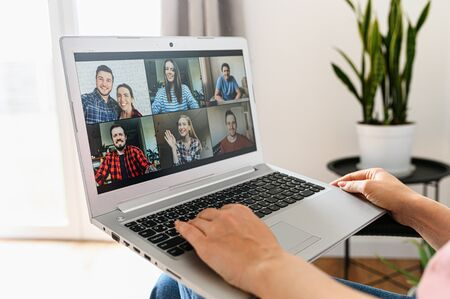 Video communication via laptop, zoom. An app for video call, online meeting with many people at the same time on the laptop screen, female hands on the keyboard. Close-up