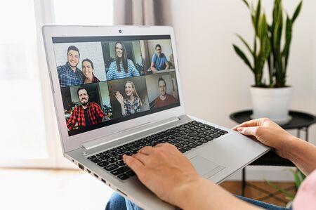 Videokommunikation über Laptop, Zoom. Eine App für Videoanrufe, Online-Meetings mit vielen Leuten gleichzeitig auf dem Laptop-Bildschirm, weibliche Hände auf der Tastatur. Nahaufnahme Standard-Bild