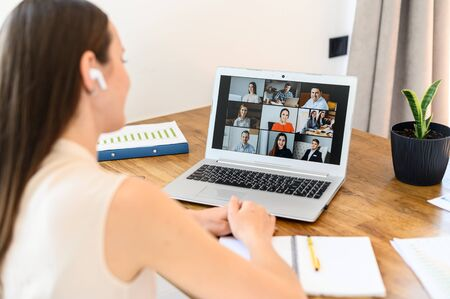 Virtual video conference, online meeting with a many employees together. A young woman is communicating via video call with coworkers, a several webcam shot of people on the laptop screen 免版税图像 - 146976284