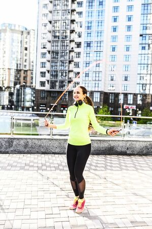 Full leigth girl in sportswear with a headphones jumps with skipping rope on the street. Outdoor cardio workout