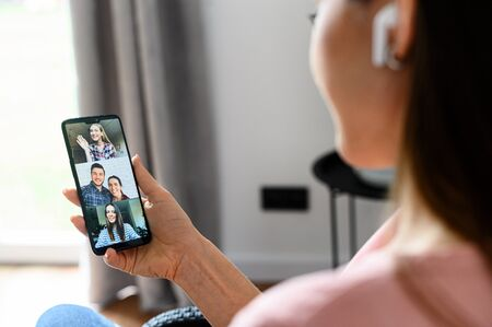 Video call via smartphone. A young woman is using phone app for video call, online meeting. She talks with a several people together in same time. Close-up back view