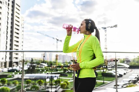 Water balance recovery during sports training. A young woman in trendy sports wear is drinking water from sports bottle, she jumps with a skipping rope outdoors Stok Fotoğraf