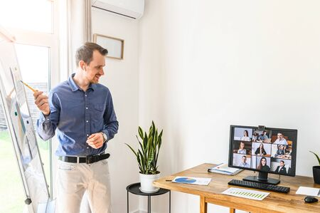 Online presentation, webinar, online meeting. A young man speaks to the audience via video call, video connection. He stands near flip chart and looks at screen with online viewers