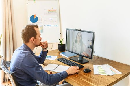 Video meeting of employees. A guy has video conference with a young woman in office