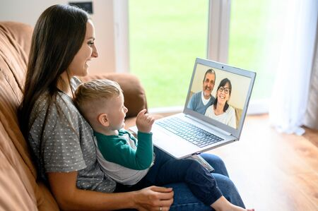 Little grandson is talking via video call on laptop with a grandparents. A young mother with a baby son sit on a sofa at home and have a video meeting grandparent are on a laptop screen Standard-Bild