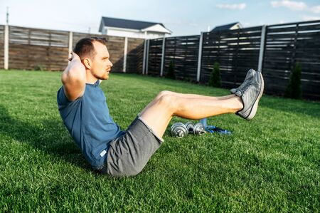 Workout without gym. A guy is training in the backyard of private house. He sits on the lawn and is doing his abs