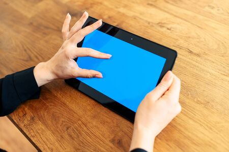 Female fingers is zooming something on tablet screen. Digital tablet with blank screen, copy space for text Stok Fotoğraf