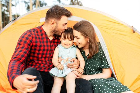 Happy friendly family spend time together in a camp among forest. A mother, a father and cute daughter sits in a tent in a hug. Active family weekend outdoors Banco de Imagens