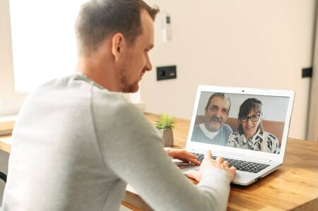 Virtual meeting with a parents. A young man is using laptop for video call to senior couple. Stock Photo