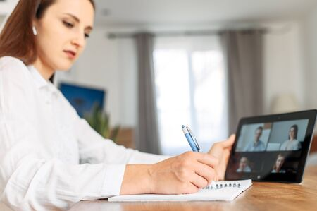 Webinars, online conference, video meeting. A young woman using app on tablet for video connect with a many people at same time together at office, she is doing notes in notebook. Distant work concept