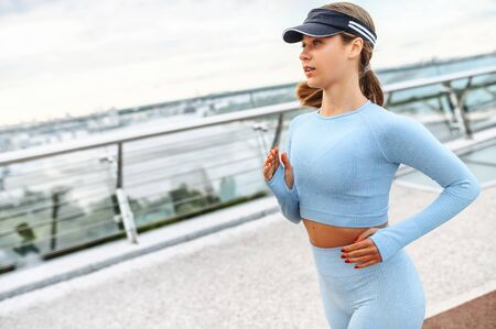 Morning jogging in the city. An athletic attractive woman in sportswear runs outdoors. Self discipline and healthy lifestyle concept