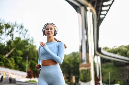 An attractive girl in the sportswear jogging outdoors with the cityscape. Morning jogging in the city. Healthy lifestyle concept Imagens