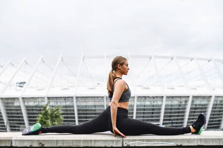 Flexibility training outdoors. A young beautiful flexible girl in trendy sports fit sits on the twine. Healthy lifestyle, stretching workout Imagens