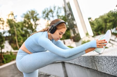 Attractive flexible girl doing stretching exercises outdoors. Healthy active lifestyle concept