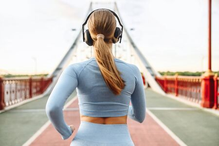 Back view of runner woman. A young slender blonde woman is jogging and listening music in headphones on a city bridge road. Healthy active lifestyle concept