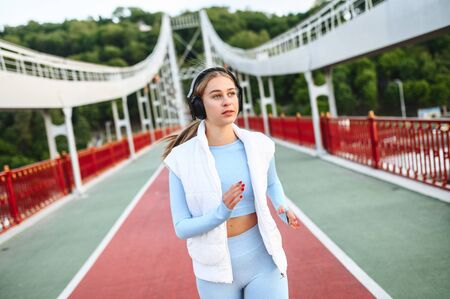 Healthy active lifestyle. Pretty athlete girl in trendy sports wear with a headphones is running on the city bridge in a sunset light Imagens