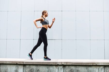 Cheerfulness for full day long. An attractive young woman is jogging outdoors. Side view. Healthy lifestyle concept