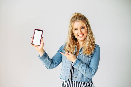 Take a look at this. Attractive young woman points finger to a blank phone screen, white wall on background. Copy space for text Standard-Bild