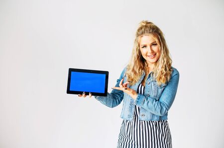 Look at this. Beautiful young woman with a tablet computer in hands stands on a white background. Woman points finger to blank tablet screen, empty space for inserting pictures, text