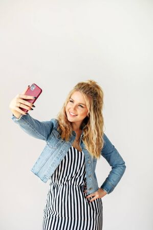 Cheerful young blonde woman is taking selfie on a fancy smartphone with a white wall on background. Photo for social networks