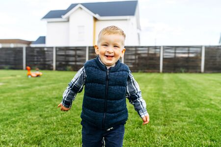 Funny child plays in the backyard. Toddler boy is running on the grass and laughing