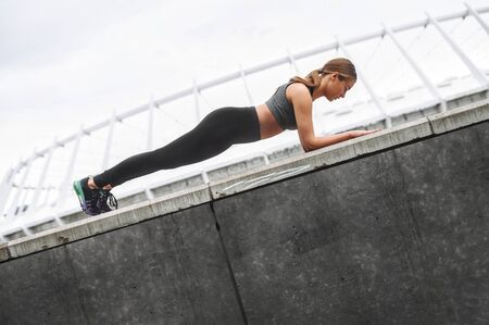 Stretching workout outdoor. Beautiful young woman in sportswear doing plank exercise. Healthy lifestyle concept Standard-Bild