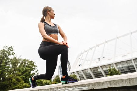 Female lower body workout. Slim and athletic girl doing lunges outdoors Standard-Bild