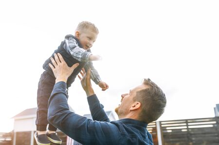 Fathers day. A young father throws his baby son up. Happy daddy and son spend time together active Standard-Bild