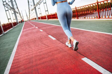 Never give up. Female legs in a sports wear and in runners sneakers on the road. Jogging, running, marathon