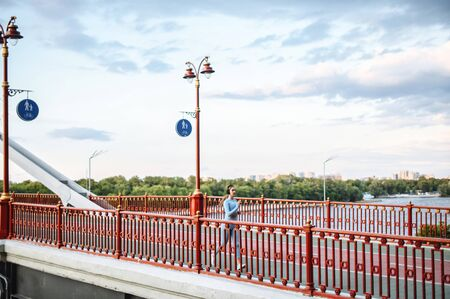 Jog in the city. Runner woman is jogging on a city bridge, the river side on background