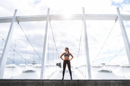Sportswoman doing full body workout on the rooftop with amazing view on a stadium. Slender athletic girl stands with hands on hips. Healthy habits, lifestyle Standard-Bild
