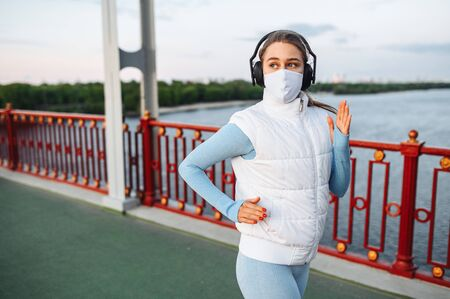 Healthy active lifestyle during pandemic. Young fitness women with a medical mask on a face running outdoors