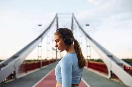 Runner woman taking a break. A slender blonde woman is standing and listening music in headphones on a city bridge road. Healthy active lifestyle concept