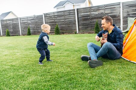 Toddler son and his father have fun in the backyard. Dad and son are camped on the lawn, daddy plays guitar, baby boy dances and laughs
