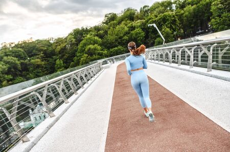 Back view of athletic woman running on the city bridge. Morning jogging. Healthy lifestyle concept Imagens
