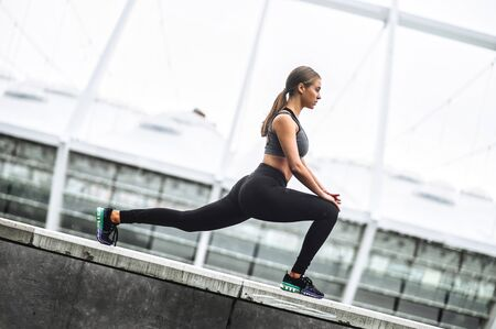 Outdoors warm-up stretch in the city. Attractive young woman doing lower body workout, lunge exercise