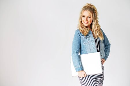 Isolated on a white background picture of attractive young woman in casual wear with a laptop, she smiles and looks away